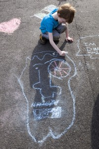 Child drawing on road with chalk