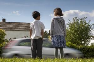 Car speeding past children