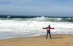 child by the sea with arms outstretched