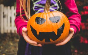 Child holding Halloween pumpkin