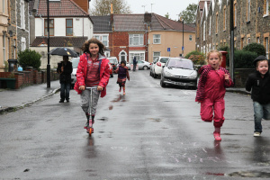 Children scooting and running in the rain in the road