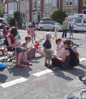 A group of adults and children sitting and playing in the road